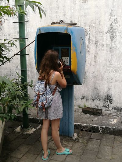Woman using telephone at booth