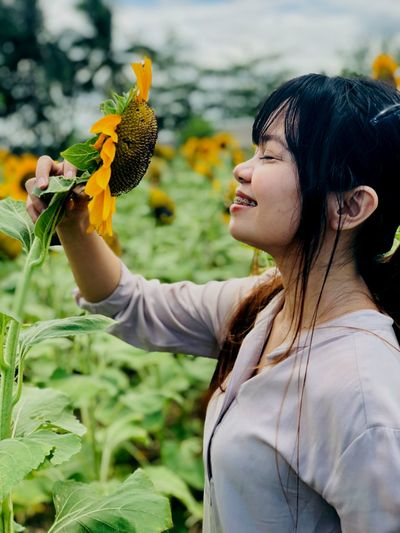 Side view of smiling young woman with eyes closed smelling sunflower