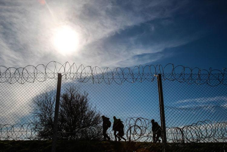 Refugees Running On Border Against Sky