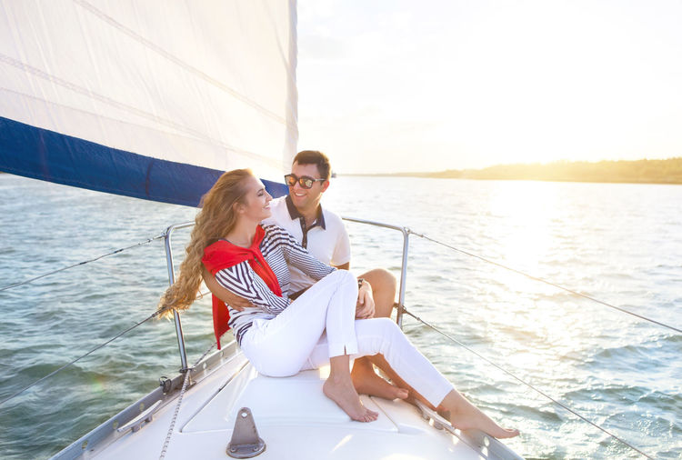 Young couple sitting on boat in sea