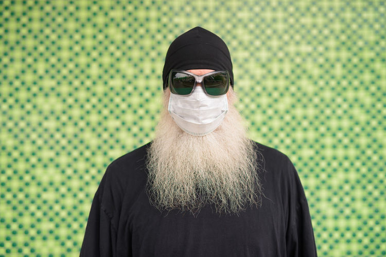 Portrait of man wearing sunglasses standing against green background