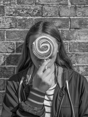 Teenage girl with lollypop in front of her face Black And White Brick Wall Candy Close-up Day English Fashion Girl Holding Human Body Part Human Hand Lifestyles Lines Long Hair Monochrome One Person Outdoors People Person Real People Stripes Pattern Teenager Unrecognisable Women Around The World Women Around The World