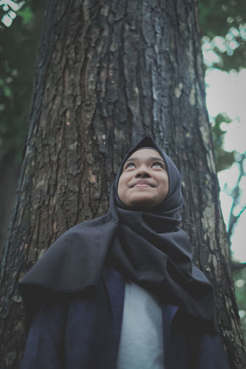 Smiling girl standing against tree trunk