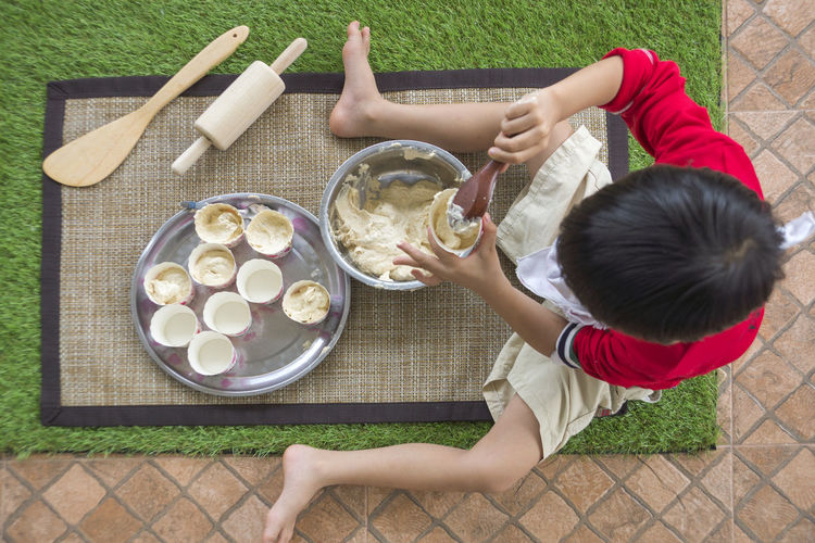 High Angle View Of Boy Filling Batter In Bowls