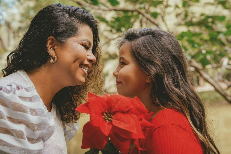 Close-up of smiling mother and daughter holding flowers outdoors