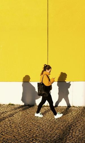 Full length of woman with umbrella against yellow wall