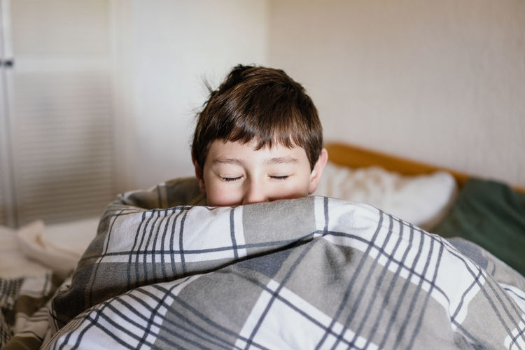 Portrait of boy relaxing on bed at home