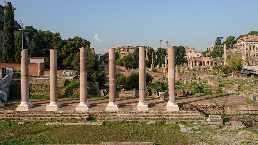 Architectural columns of roman forum against sky