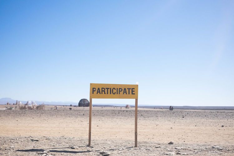 Information sign on desert against clear sky