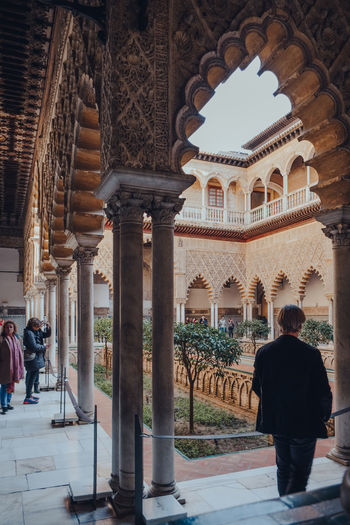 Rear view of people walking in historic building