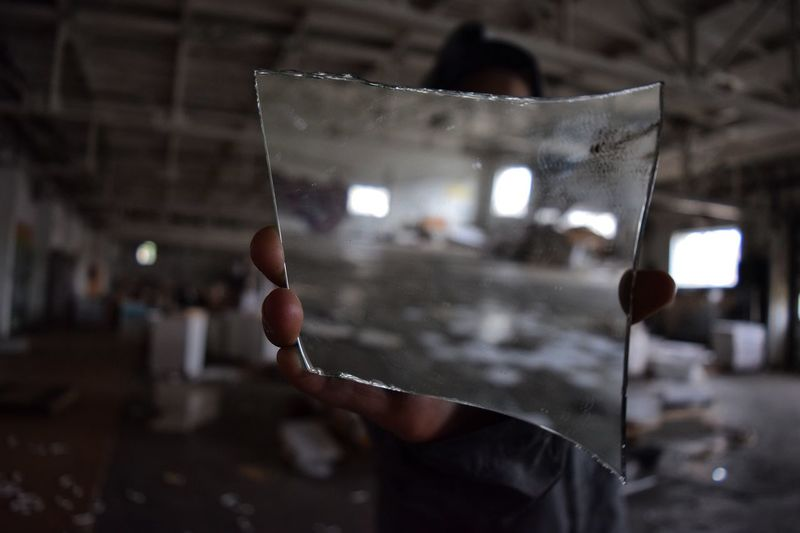 Person holding piece of mirror while standing in abandoned building