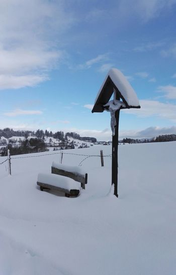 Frozen Crucifix And Snow Covered Bench Against Sky