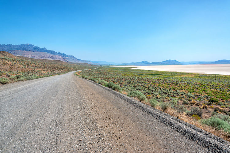 Scenic view of road amidst land against sky