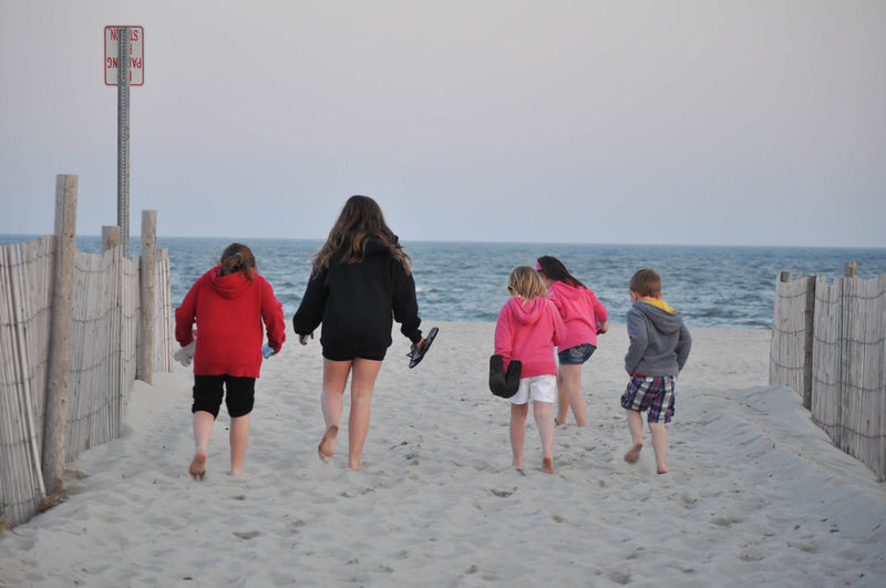 Group of Children Walking on the Beach Towards the Ocean Beach Full Length Horizon Over Water Leisure Activity Lifestyles Nature Outdoors People Real People Rear View Sand Sea Standing Vacations Water