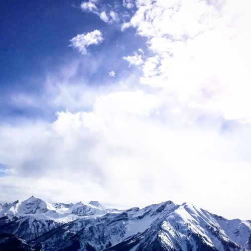 Low angle view of snowcapped mountains against sky