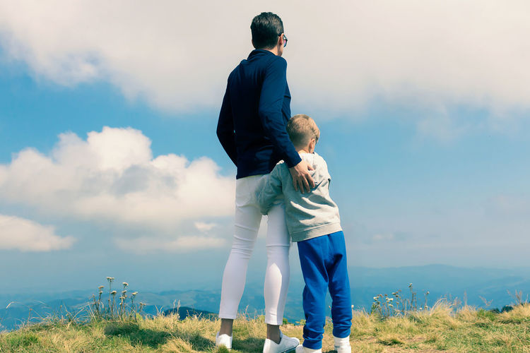 Full length of father with daughter standing against sky