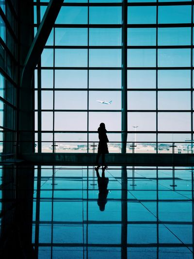 Silhouette woman standing at airport terminal