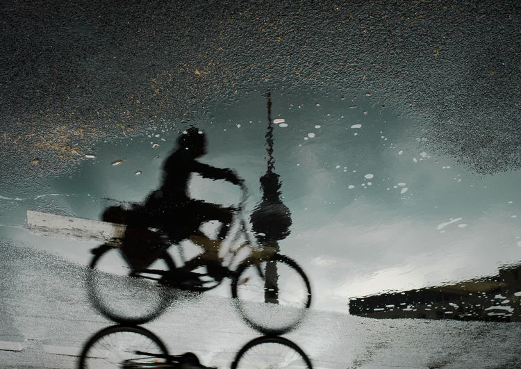 Upside down image of woman riding bicycle reflecting in puddle