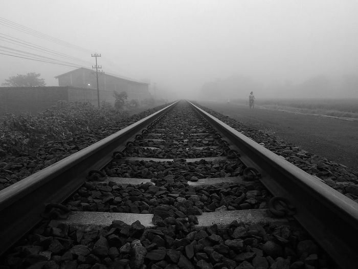 Railroad tracks against sky in foggy weather
