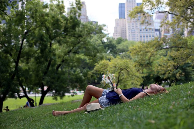 Side view of young woman relaxing in park