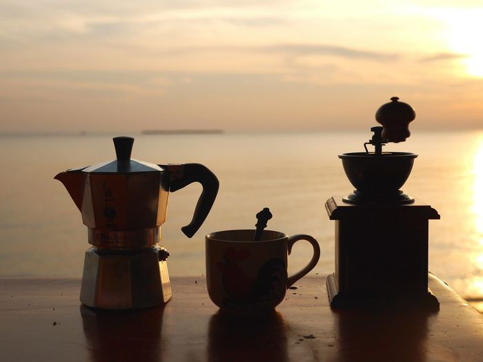 Close-Up Of Coffee On Table Against Sea During Sunset