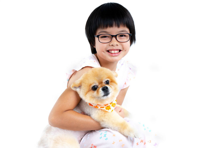 Isolated portrait Asian little girl holding Pomeranian dog with care on white background. Studio shot of girl and puppy Domestic Pets Domestic Animals Mammal One Animal Animal Themes Canine Portrait Dog Looking At Camera Animal Eyeglasses  One Person Smiling Happiness Pet Owner Front View Studio Shot White Background Funny Adorable Dog Friendship Isolated