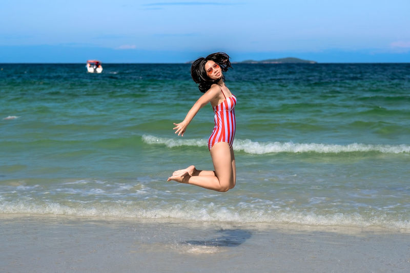 Portrait of woman jumping at beach