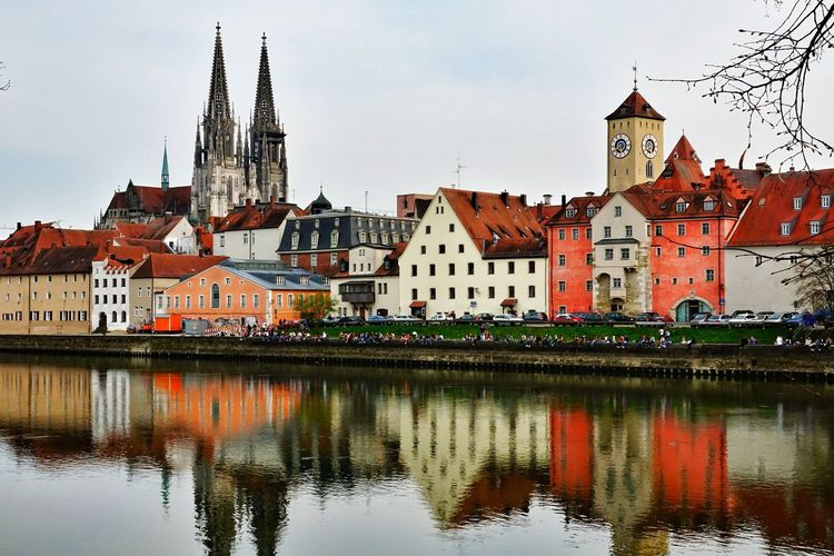 Reflection of regensburg cathedral and buildings on danube river