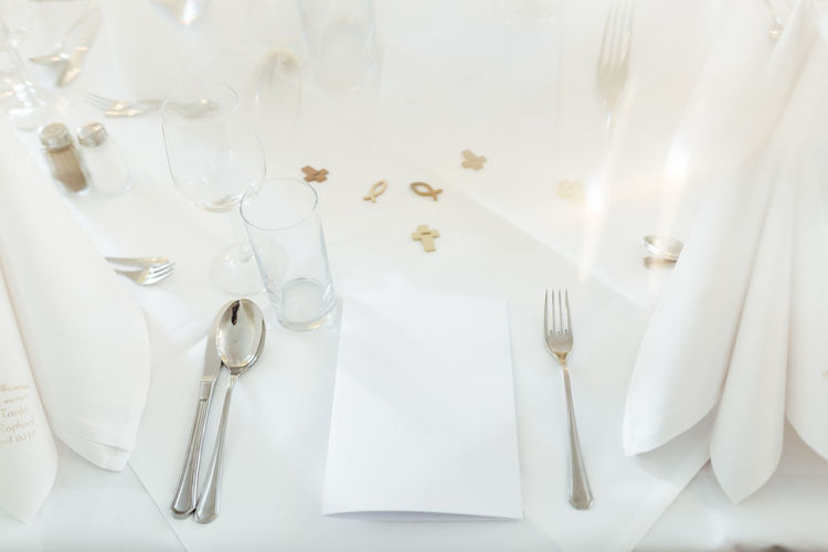 Catholicism Christianity Symbolism Indoors  Table Knife Eating Utensil White Color Knife No People Fork Kitchen Utensil Still Life Spoon Place Setting Setting Table Celebration Plate Silverware  Glass Arrangement High Angle View Silver Colored Crockery Luxury Copy Space No Text Reflection