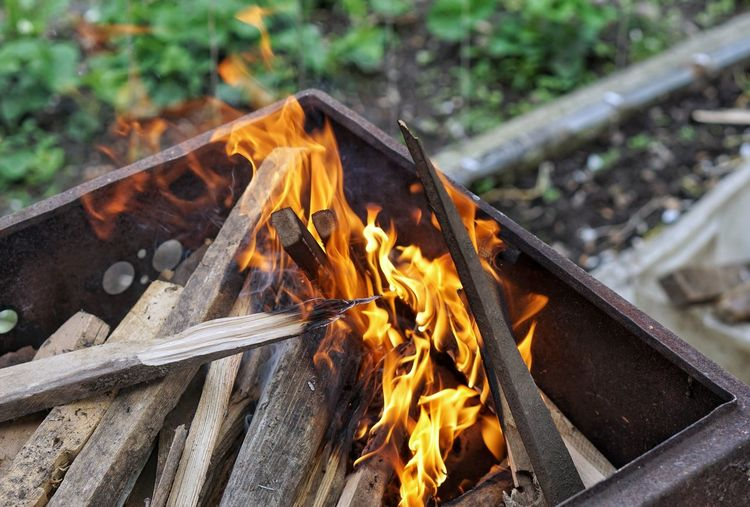 High angle view of firewood burning in fire pit