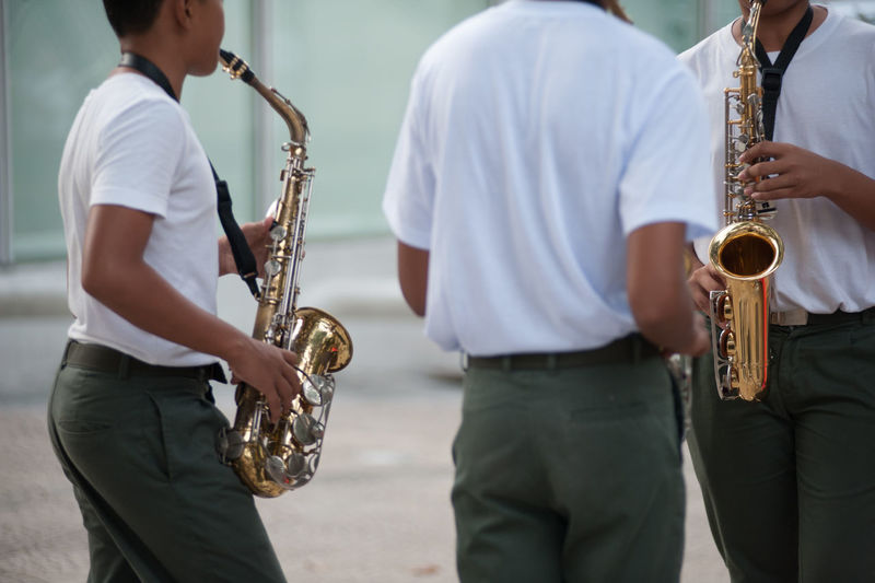 Midsection Of Street Musicians Plying Saxophone