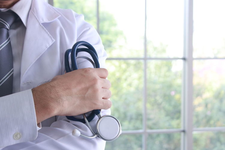 Midsection Of Doctor Holding Stethoscope While Standing Against Window