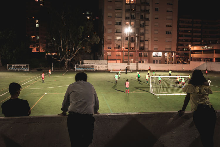 People playing soccer on field at night