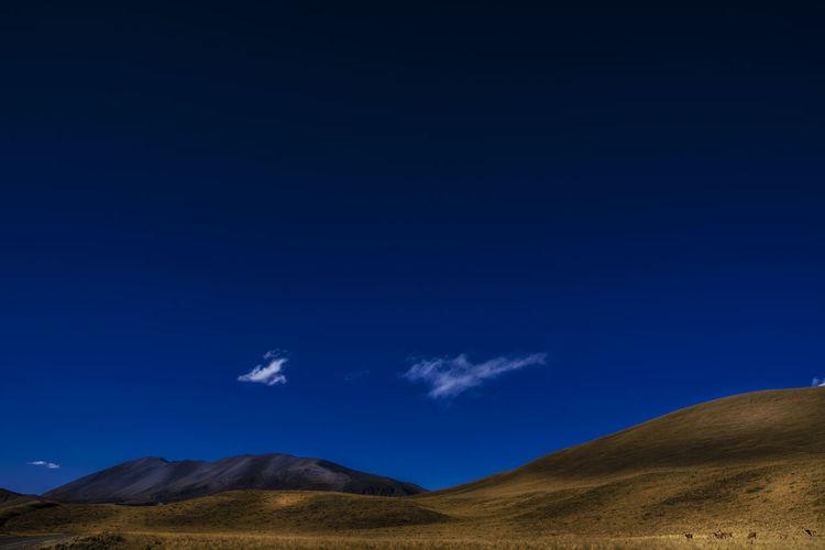 Scenic view of arid landscape against blue sky