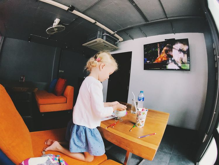 Casual Clothing Child Childhood Females Girls Hairstyle Holding Home Interior Indoors  Innocence Leisure Activity Lifestyles One Person Real People Sitting Standing Table Three Quarter Length Women