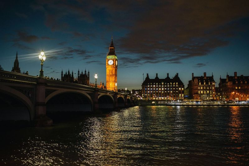 Illuminated Big Ben With Westminster Bridge Over Thames River Against Sky At Night