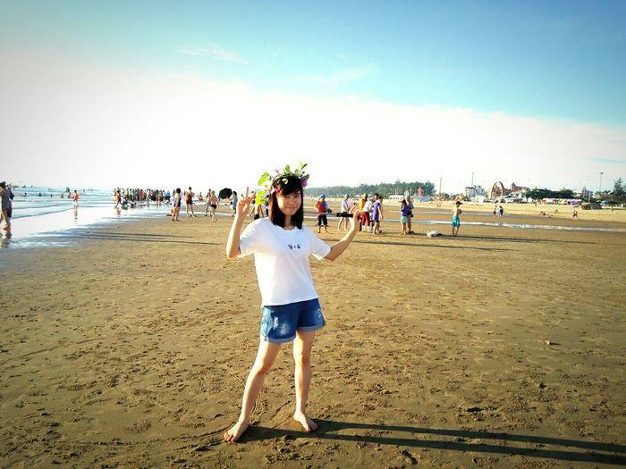Full length portrait of smiling girl standing at beach against sky