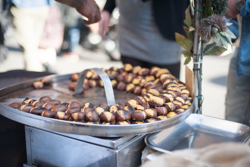 Close-up of roasted chestnut in container at market