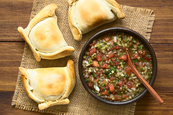 Chilean Pebre sauce, a traditional condiment made of tomato, onion, garlic, spicy aji pepper and coriander with empanadas on the side, photographed overhead on dark wood with natural light Aji Chile Chilean  Filled Salad Stuffed Accompaniment Baked Chilean Food Cilantro Condiment Coriander Empanada Empanada De Pino Food Food And Drink Meat Onion Pastry Pebre Pepper Salsa Sauce Snack Tomato