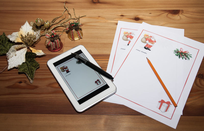 High Angle View Of Digital Tablet With Christmas Greeting Cards On Table