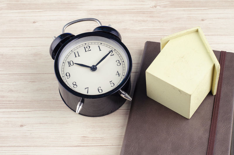 flat lay working desk with alarm clock, diary and house miniature over wooden background. Time Table Clock Still Life Wood - Material Indoors  High Angle View No People Alarm Clock Geometric Shape Close-up Food And Drink Number Food Wood Circle Directly Above Paper Shape Minute Hand