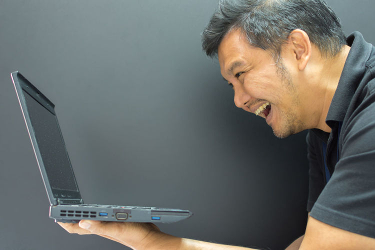 Close-up of man looking at laptop against black background
