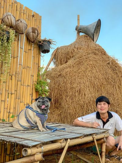 Portrait of woman sitting with dog by hay
