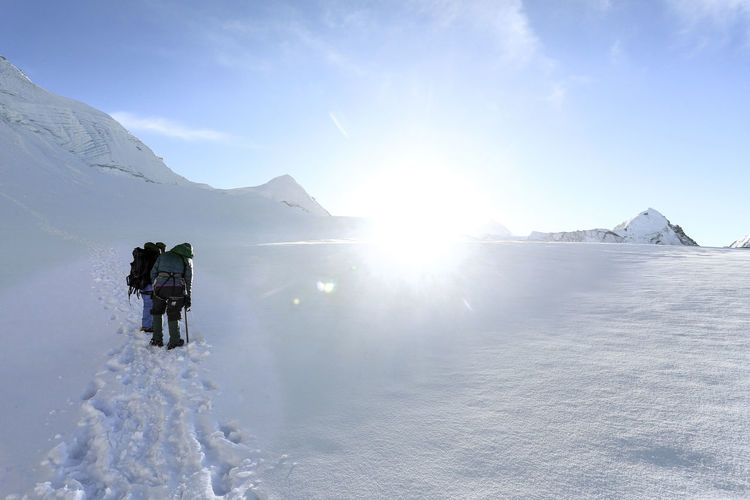 Hikers carrying backpack while standing on snow covered mountain
