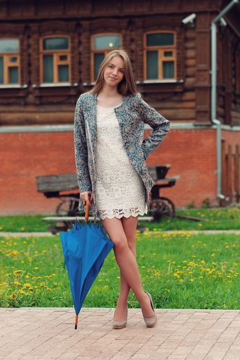 Full length portrait of beautiful young woman holding umbrella on footpath against building