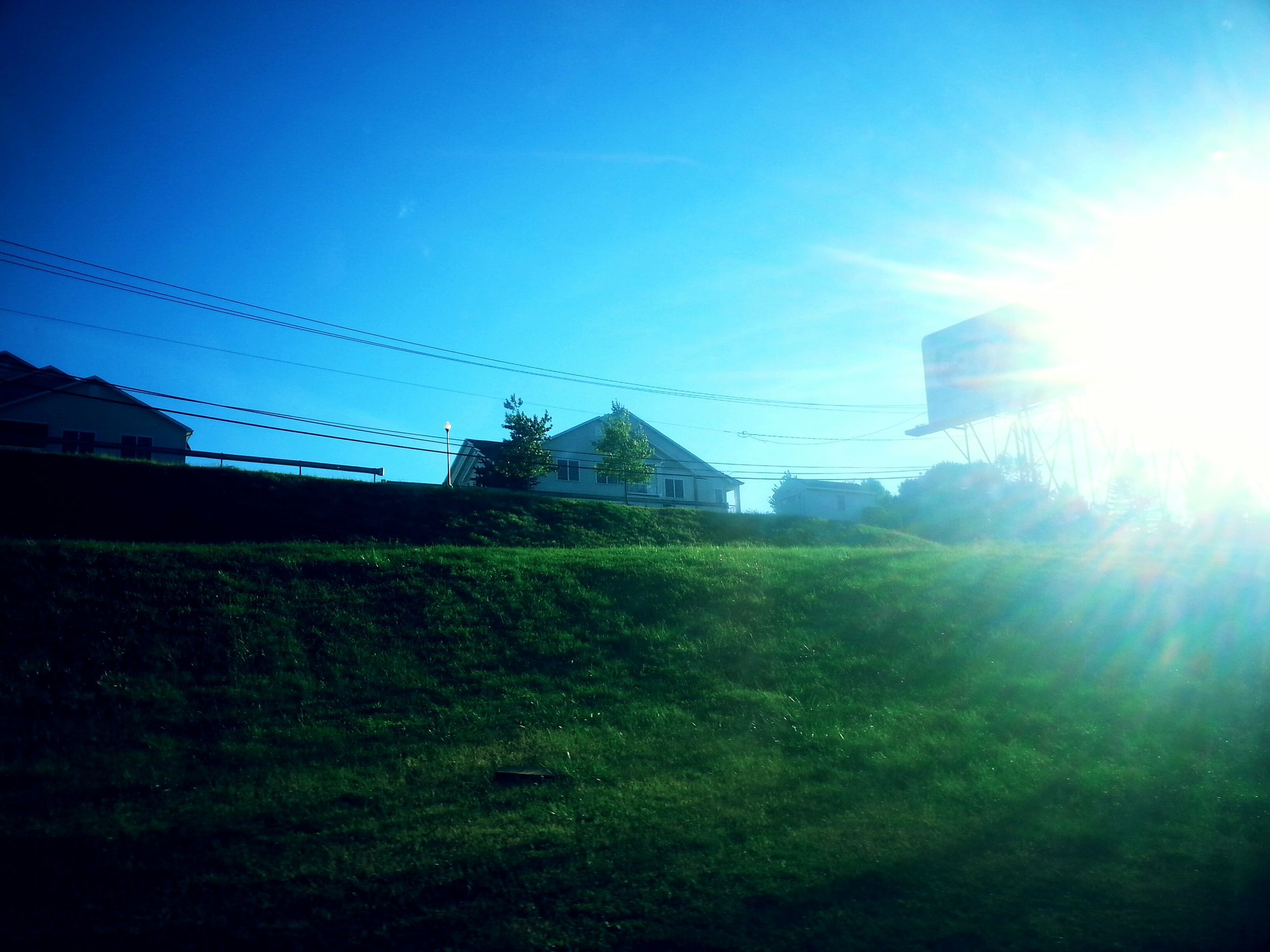building exterior, architecture, built structure, sun, sunlight, sunbeam, house, lens flare, sky, blue, clear sky, low angle view, grass, power line, outdoors, field, no people, residential structure, bright, nature