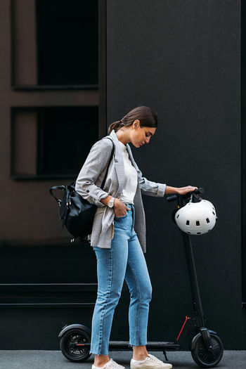 Woman holding umbrella while standing at home