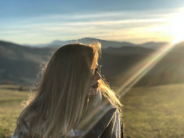 Woman looking at mountain range against sky