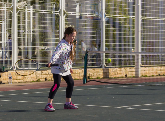 Full Length Of Girl Playing Tennis In Court