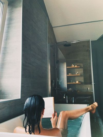 Rear view of woman reading book in bathtub at home